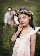 Portrait of a liitle, cute girl posing in the summer garden