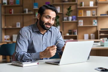 Young bearded indian business man teacher talking, teleworking, having virtual classroom meeting working on laptop computer giving online webinar training, remote class on video conference call.