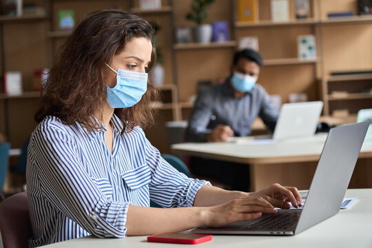 Latin girl student wearing face mask studying on laptop. Hispanic professional woman employee in facemask working sitting at table in modern office coworking space keeping safe social distance.