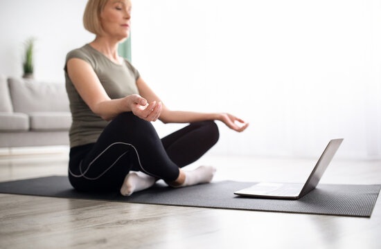 Balanced mature woman meditating with closed eyes in front of laptop at home, selective focus