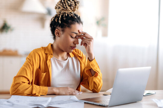 Overworked frustrated young african american student girl or freelancer, in casual clothes, studying or working at home uses laptop, thinking about a problem taking break experiencing stress need rest