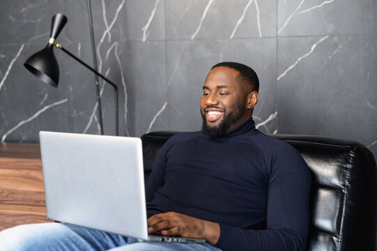 African American male IT specialist sitting on large soft armchair, looking at laptop screen. Happy black man reading message email with good news, chatting with clients online, working remotely