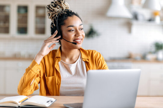 Joyful contented friendly young African American woman with dreadlocks and headphones, support operator, call center employee, working at laptop, advises clients online, looking away, smiling