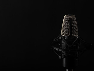 Studio microphone in studio on a black background.Advertising school vocals, readings te text, podcasts