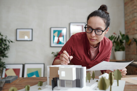 Young elegant female architect with paper and pen bending over model of new house and yard and pointing at roof while working over project