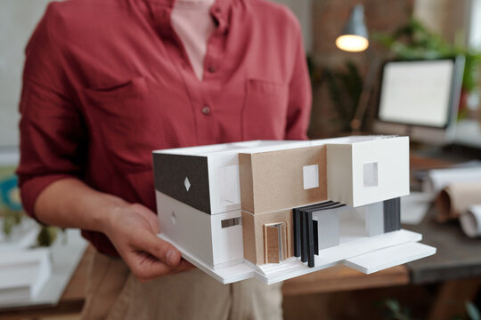 Hand of young female architect or engineering designer in casualwear holding paper model of new house while standing in office