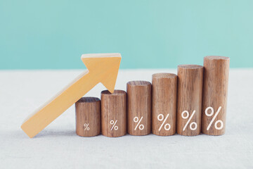 Wooden blocks with percentage sign and arrow up, financial growth, interest rate and mortgate rate...