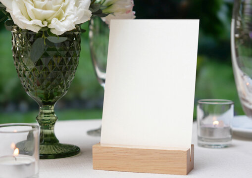 Mockup white blank space card, for greeting, table number, wedding invitation template on wedding table setting background. with clipping path