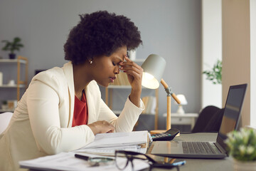 Obraz Feeling tired and stressed, workload, burnout and fatigue. Frustrated young african american woman keeping eyes closed and massaging nose after working at laptop for long time in office - fototapety do salonu