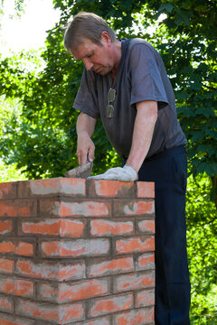 Senior man is making a chimney of red bricks, working with a trowel and making masonry works on a roof of a house, vertical