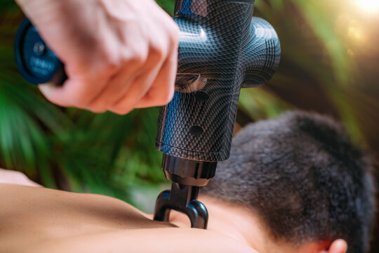 Therapist Treating Patient's Trapezius with Massage Gun with Fork Head