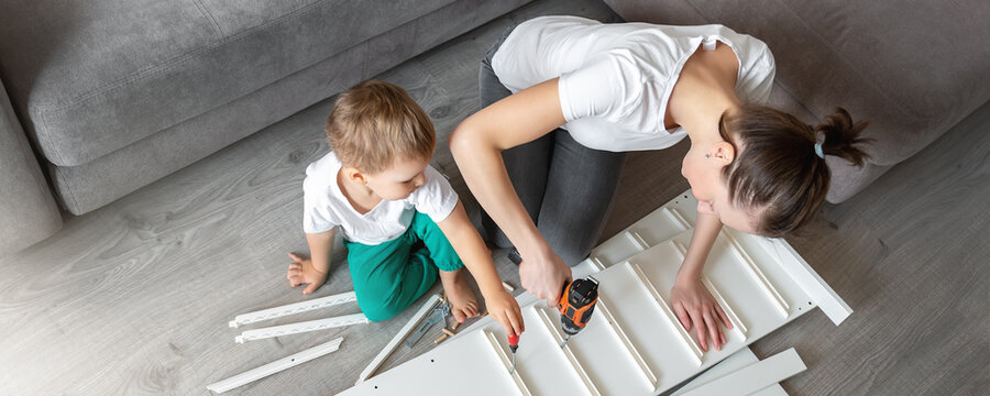 Cute adorable caucasian toddler boy kid sit on floor and help mom assembling furniture shelf with power screwdriver tool. Young adult mum with funny little child enjoy playing at home indoors