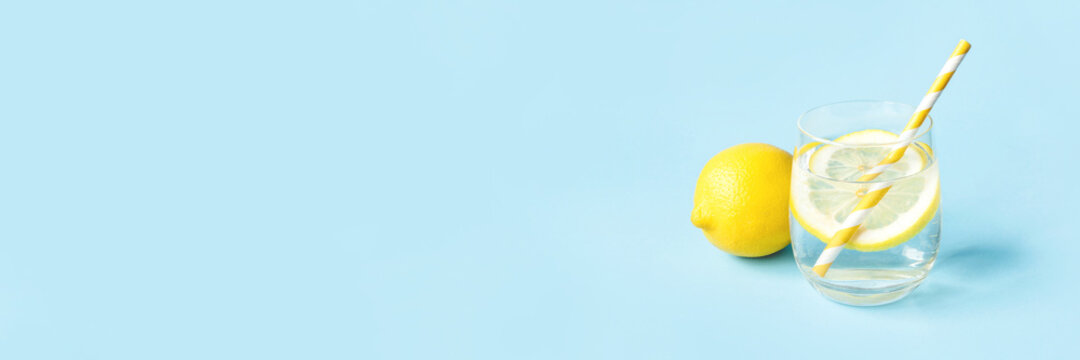 Glass of water with lemon on a blue background. Summer refreshing drink.