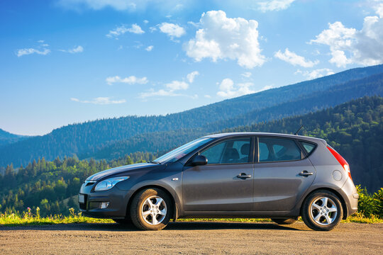 mizhhirya, ukraine - AUG 08, 2020: car on the concrete parking on top of the mountain in morning light. travel countryside concept. beautiful nature scenery views in summer with clouds on the blue sky