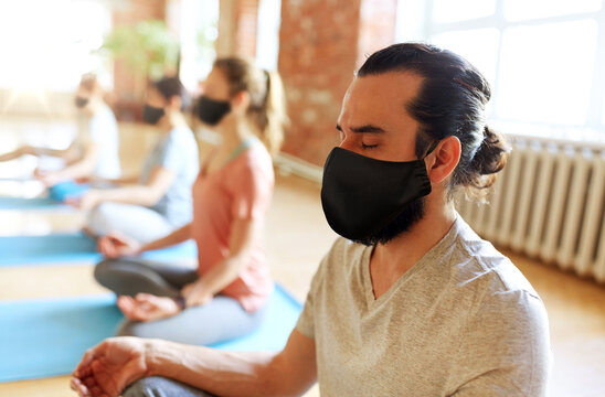 fitness, yoga and health care concept - man with group of people wearing black face protective masks for protection from virus disease meditating in lotus pose at studio