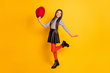 Full length body size view of charming trendy cheerful girl holding in hand hat dancing having fun isolated on bright yellow color background