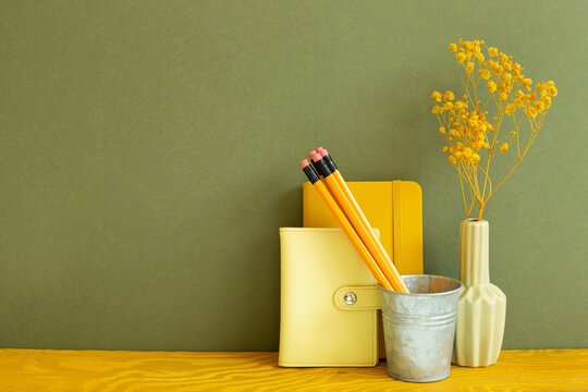 Notebook, pencil, vase of dry flower on wooden desk. Khaki background. Work and study place