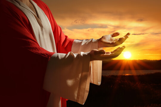 Jesus Christ reaching out his hands and praying at sunset