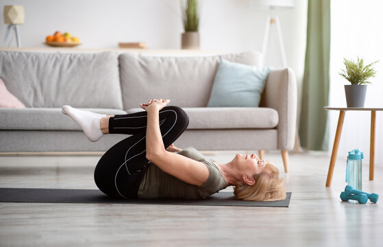 Sporty senior woman doing exercises on yoga mat indoors, blank space