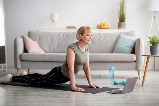 Domestic yoga. Flexible mature lady doing cobra asana on sports mat, training to online tutorial on laptop, indoors