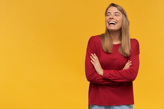 Laughing happy girl, turned to the left side, stands with folded arms isolated on a yellow background. Funny joke, pleasant moment, free space for your advertisement