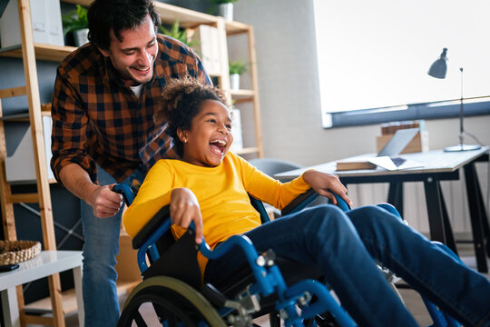 Multiethnic happy family activities with disabled handicapped child in wheelchair
