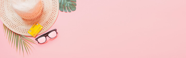summer accessories concept from credit card and summer collection on pastel red background. web banner size.