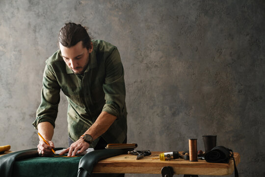 Bearded focused craftsman working with leather while standing at table