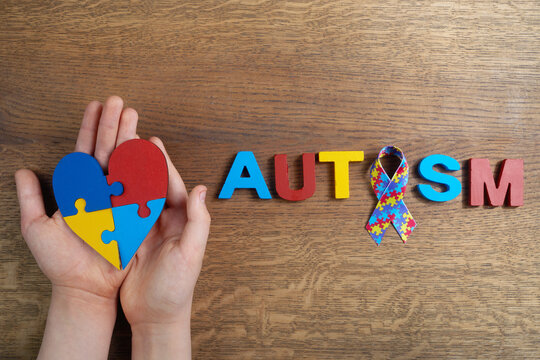 Autistic boy hands holding heart shapeed puzzle with word autism and awarennes ribbon on wooden background. Autism awareness day or month.