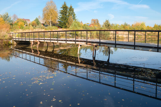 View of the water channel in the village and the bridge on an autumn sunny day