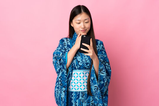 Young Chinese girl wearing kimono over isolated background thinking and sending a message