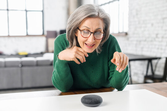Contemporary retired woman using voice commands to control smart speaker, mature woman talking to the digital virtual assistant at home, asking a question or requesting to switch music
