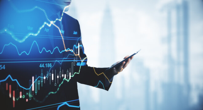 Businessman holding mobile phone in his hand, trade charts, trading concept