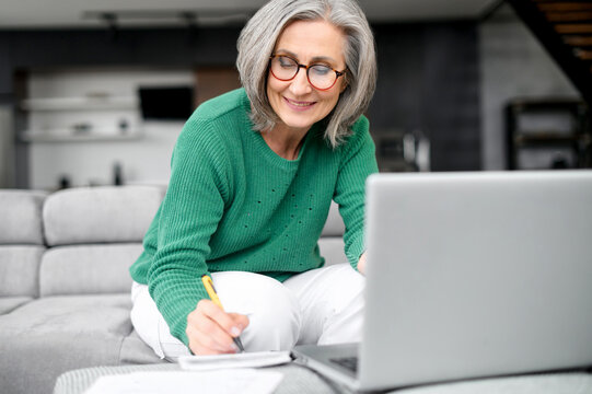 Confident mature woman using laptop computer for remote work, watching webinar and taking notes sitting at home. Contemporary senior female online teacher holding video conference and making marks