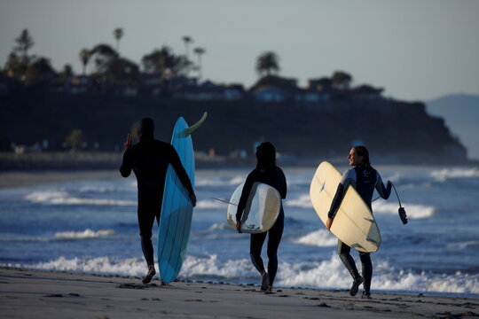 Surfers leave the ocean after riding early morning waves at Cardiff State Beach in California