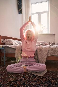 Girl sitting cross-legged and enjoying meditation in her bedroom