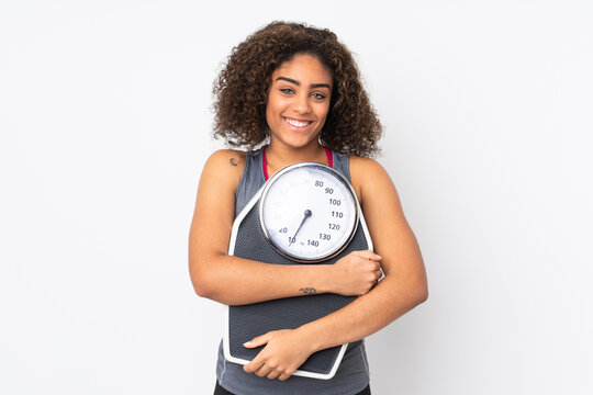 Young African American woman isolated on white background with weighing machine