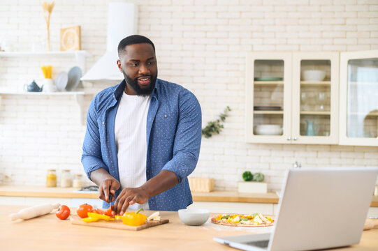 Focused handsome African American guy watching cooking classes and learning how to make delicious vegan dinner lunch watching video blog course from laptop in the modern kitchen, chopping veggies