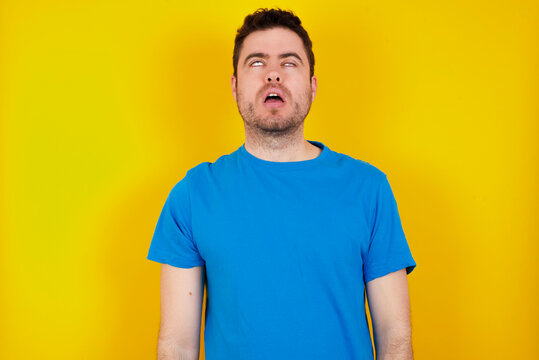 young handsome caucasian man wearing blue t-shirt against yellow background looking sleepy and tired, exhausted for fatigue and hangover, lazy eyes in the morning.