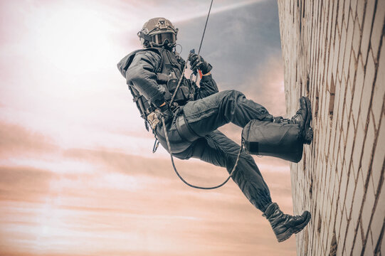 Special forces fighter descends from a skyscraper to storm the apartment. SWAT, police, counter terrorism concept.
