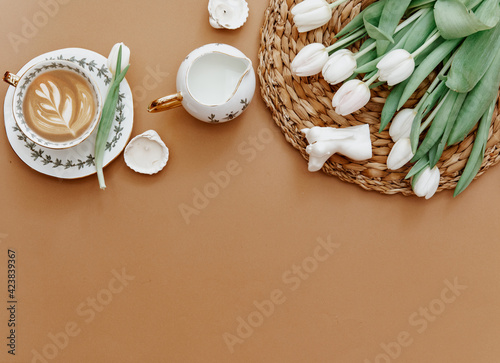 Easter, spring, 8 march, mother day, still life scene. White tulips and coffee cup on brown background, top view, flat lay, copy space