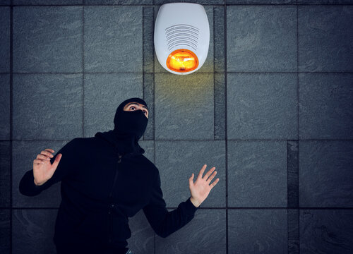 Thief with balaclava was spotted trying to steal in a apartment from the security alarm system. Scared expression