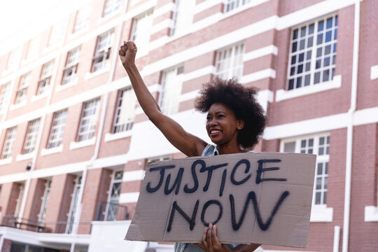 African american female protester on march holding a homemade protest sign raising fist and smiling
