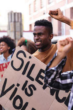 African american man with protesters on march holding signs and raising fists
