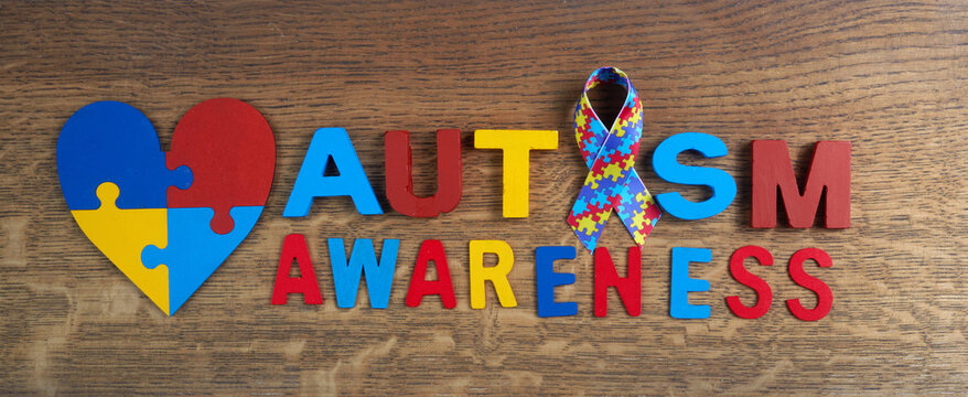 Autism awareness. Autism awareness ribbon, heart and word autism on wooden background background.