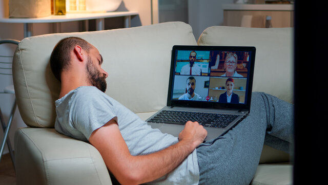 Comfortable man in pajamas falling asleep while chatting with collegues during online business videocall using laptop computer. Caucasian male sitting on couch late at night in kitchen