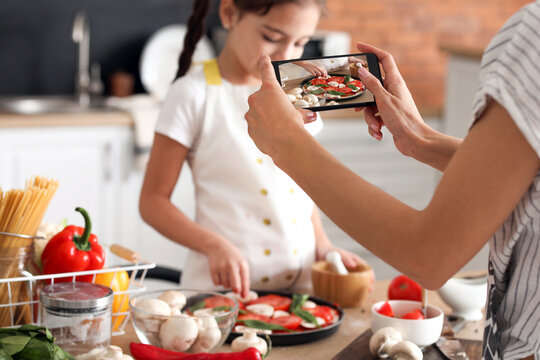 Female food photographer with mobile phone and little girl cooking pizza in kitchen