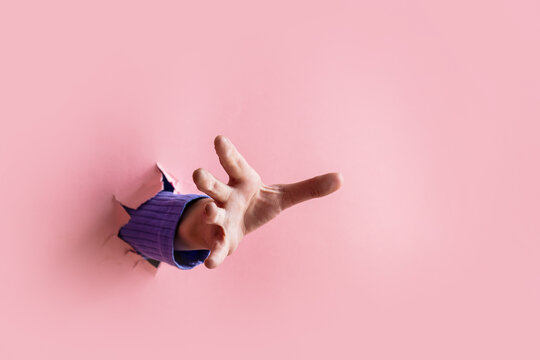 female hand trying to catch something sticking out from pink background
