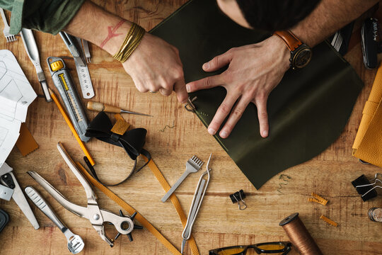 White craftsman working with leather at wooden table in workshop