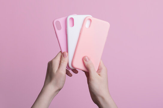 hands holding three colorful smartphone iPhone X cases isolated on pink background